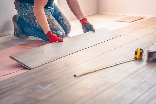 A professional home remodeling contractor installs hardwood flooring in a client's home.