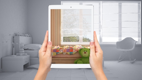 A gray background for a kids bedroom gets coloring through the lens of a tablet held in front of the room.