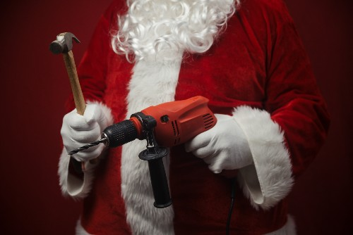 A man dressed in a santan outfit has a hammer and a power tool ready for a winter renovation project.